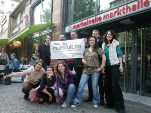 Voll gut drauf - auch ohne Bezahlung: Ehrenamtliche Mitarbeiter von radio multicult.fm vor der Marheineke Markthalle in Kreutberg.